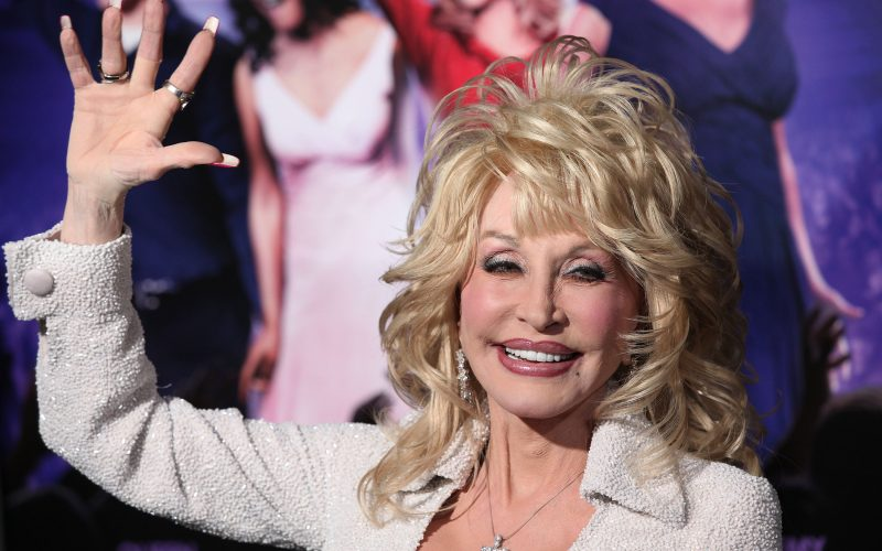 A photograph of Dolly Parton waving