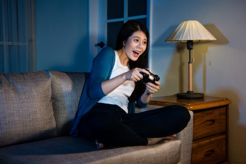 A woman sitting on a couch plays a video game.