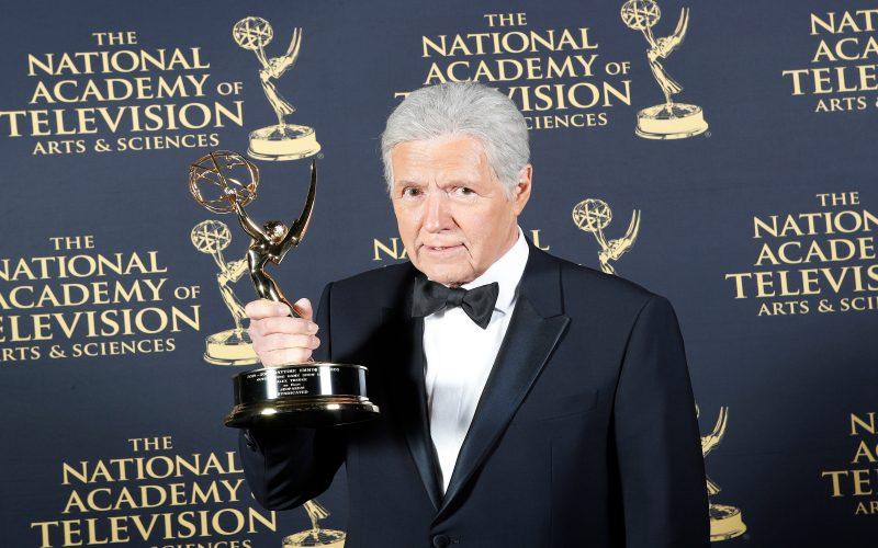 Jeopardy! host Alex Trebek holding one of his Emmy Awards.