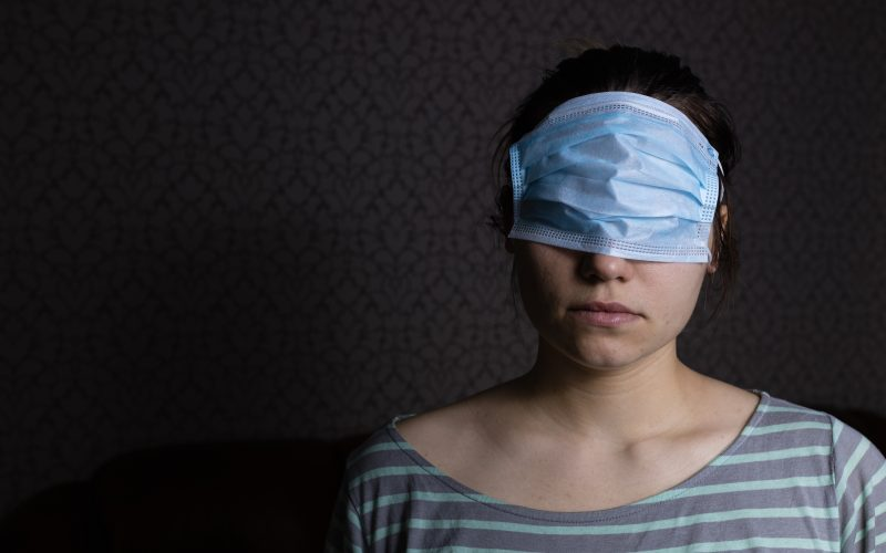 A woman wears a respiratory mask over her eyes.