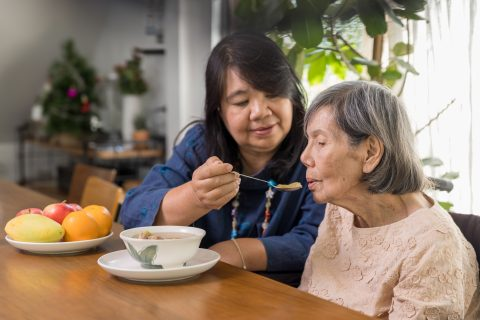 A woman feeds a senior citzen a bowl of soup while sitting at a dining room table.