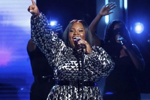 Tasha Cobbs Leonard performs onstage singing into a microphone