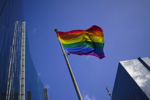 A rainbow flag flutters in the wind