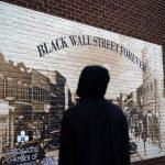 A man looks at a Black Wall Street mural in the historic Greenwood neighborhood of Tulsa, Oklahoma.
