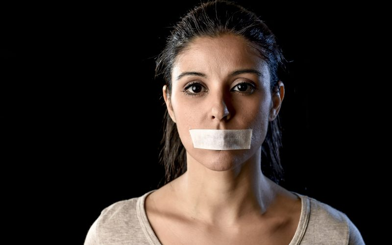 A woman with tape over her mouth