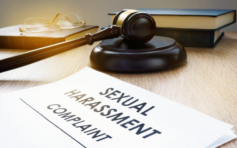 """A judge's gavel sits by a note that reads: """"sexual harassment complaint."""""""