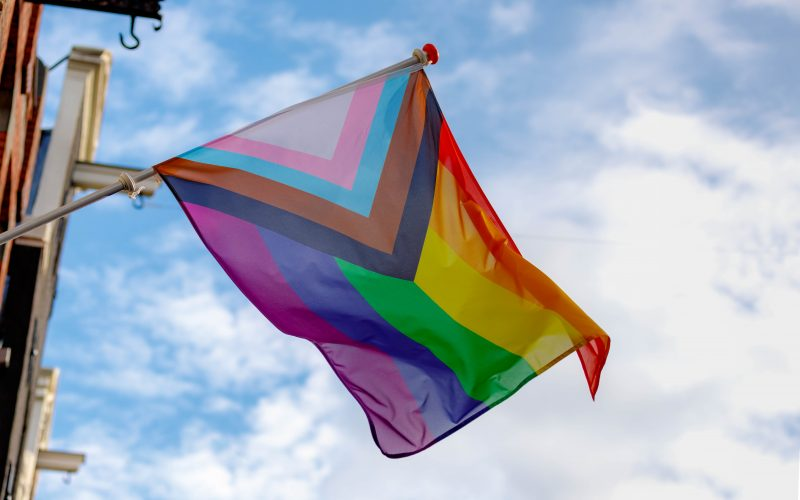 A pride flag hangs from a building.