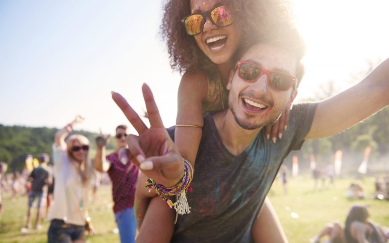 Two friends pose for a photo at a festival.