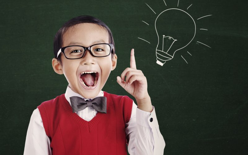 A boy wearing a sweater vest and a bow tie looks like he just had a great ideas as he points at a chalkboard.