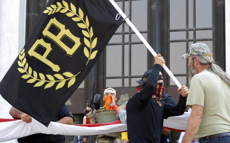 A protester carries a Proud Boys banner, a right-wing group, while other members start to unfurl a large U.S. flag in front of the Oregon State Capitol in Salem, Ore.