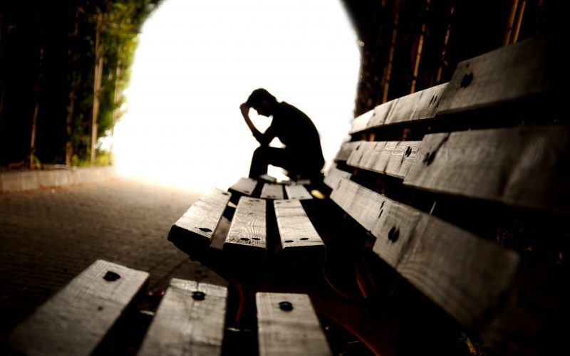 A teen sitting on a bench, looking down.