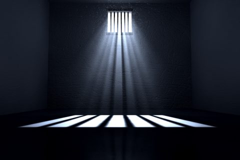 An old jail cell interior with barred up window with light rays penetrating through it reflecting on the floor.