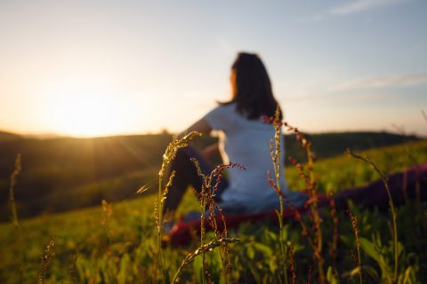 Blurred image of woman relaxing in nature, watching the sunset.