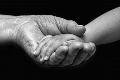Image of an elderly woman and baby hands.