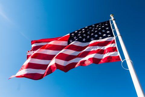 American flag waving in blue sky.