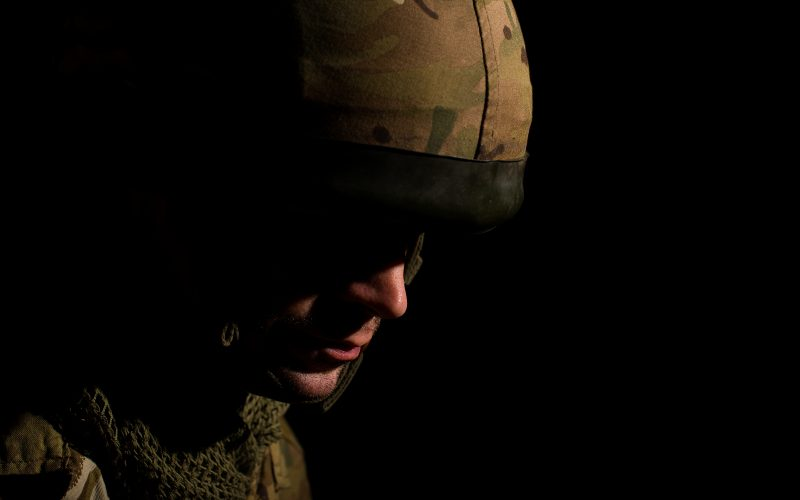 A man dressed in military attire stares at the ground.