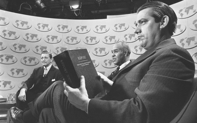 """Sen. Fred R. Harris (D-Okla.), holds a copy of the report of the National Advisory Commission on Civil Disorders as he and two other members of the commission discuss the study on the television-radio program """"Issues and Answers,"""" in Washington, March 3, 1968. With him are the commission's chairman, Gov. Otto Kerner of Illinois, right, and Roy Wilkins, center, executive director of the NAACP."""