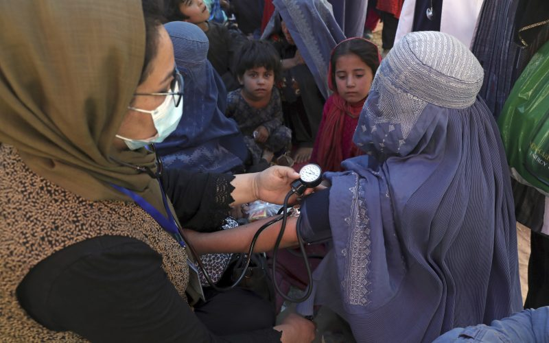 In this Aug. 10, 2021 file photo, an internally displaced woman from northern provinces, who fled her home due to fighting between the Taliban and Afghan security personnel, has her blood pressure taken after taking refuge in a public park in Kabul, Afghanistan.