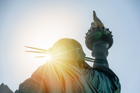Photo of the Statue of Liberty in the sunset.