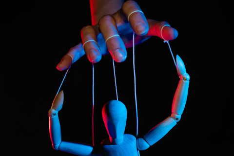 Photo illustration of a marionette in human hand.