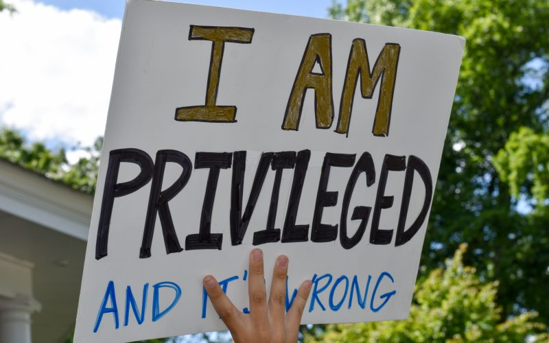 """A High School Student Holding Up A Sign That Says """"I Am Privileged And It's Wrong."""""""