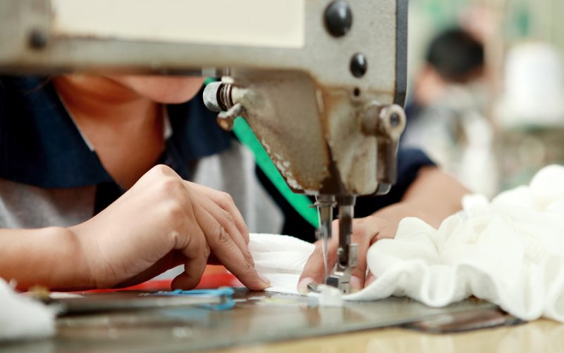 A portrait of worker using industrial sewing machine at garment factory.