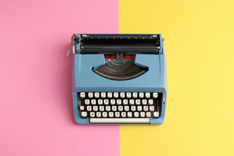 A typewriter on a colorful background.