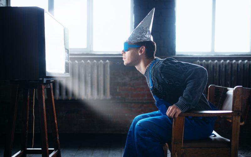 Photo illustration of man in tinfoil helmet and glasses.